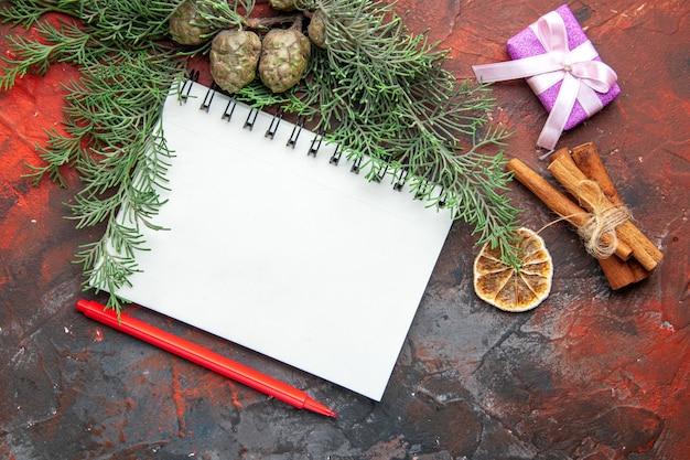 Bovenaanzicht van sparren takken paarse kleur geschenk en gesloten spiraal notebook kaneel limoenen op rode achtergrond
