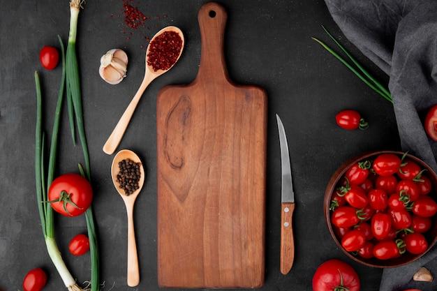 Bovenaanzicht van specerijen met lente-uitjes tomaten knoflook en snijplank op zwarte ondergrond