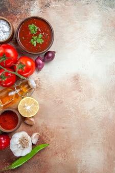Bovenaanzicht van specerijen saus kruiden tomaten citroen uien knoflook fles olie
