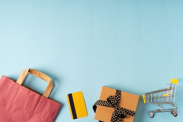 Bovenaanzicht van speelgoed winkelwagentje, dozen, creditcard, zwarte papieren zak en cadeau op blauwe achtergrond.
