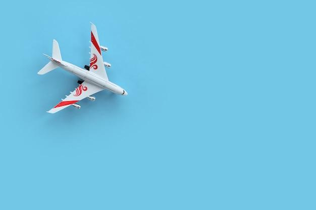 Bovenaanzicht van speelgoedvliegtuig op een blauwe achtergrond met kopieerruimte