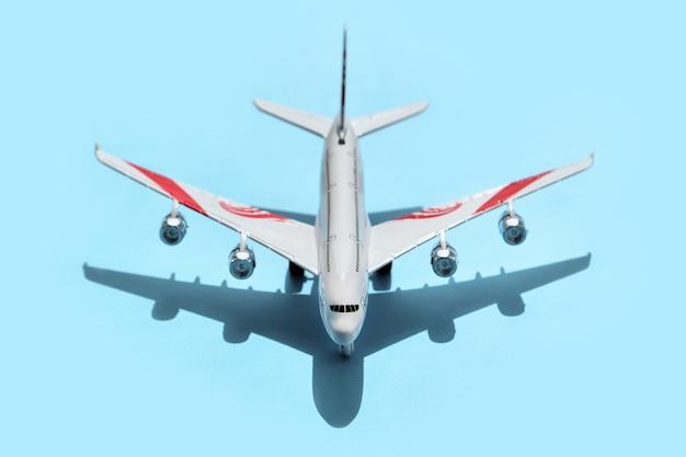 Bovenaanzicht van speelgoedvliegtuig op een blauwe achtergrond