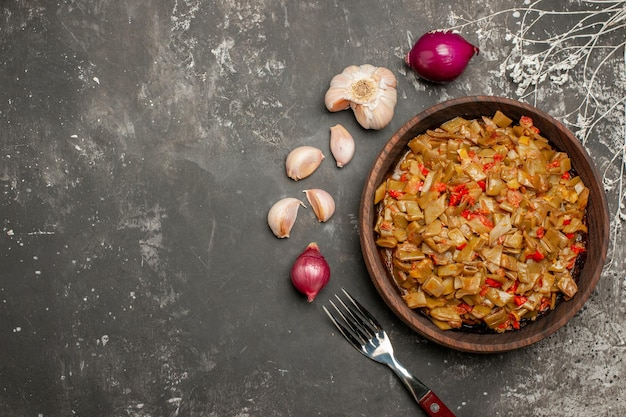 Bovenaanzicht van sperziebonen met tomaten houten bord met sperziebonen en tomaten naast de ui, knoflook en vork op tafel