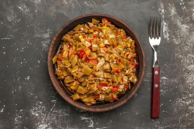 Bovenaanzicht van sperziebonen, tomaten en sperziebonen in de kom naast de vork op de donkere tafel