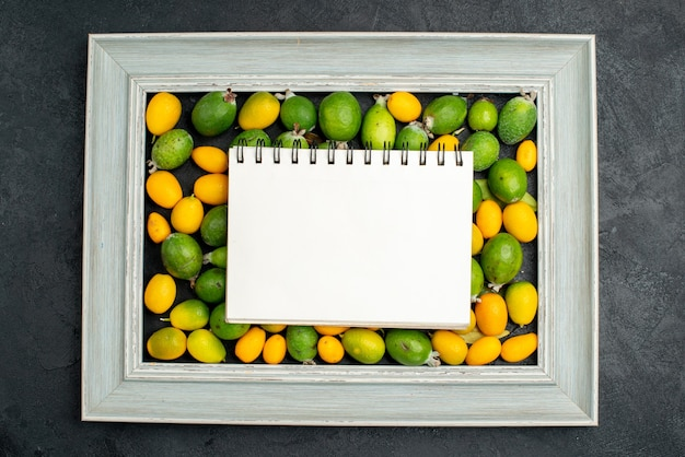 Bovenaanzicht van spiraalvormig notitieboekje over het verzamelen van citrusvruchten op fotolijst op donkere achtergrond