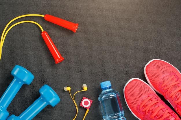 Bovenaanzicht van sportartikelen, halters, een springtouw, een fles water, sneakers en een speler