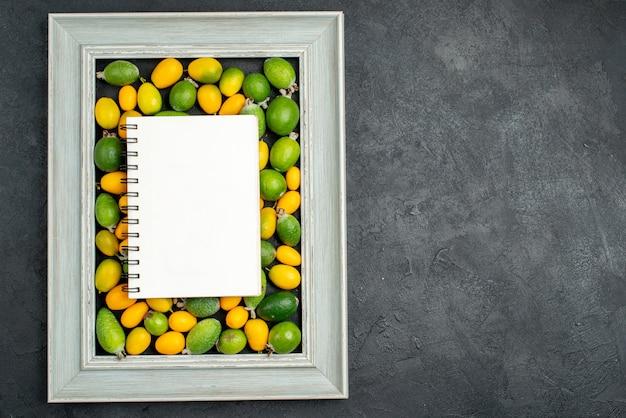 Bovenaanzicht van spral-notitieboekje op verzameling citrusvruchten in fotolijst aan de rechterkant op donkere tafel