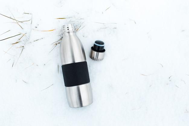 Bovenaanzicht van stalen herbruikbare thermoskan en dop van de fles op sneeuw.