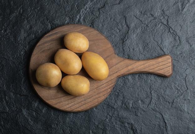 Bovenaanzicht van stapel aardappelen op houten snijplank.