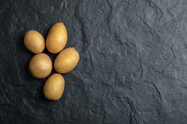 Bovenaanzicht van stapel aardappelen. verse aardappelen op zwarte stenen achtergrond.