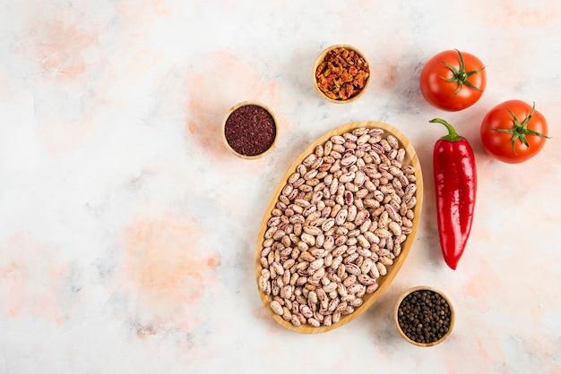 Bovenaanzicht van stapel bonen met verschillende soorten kruiden en verse tomaten.