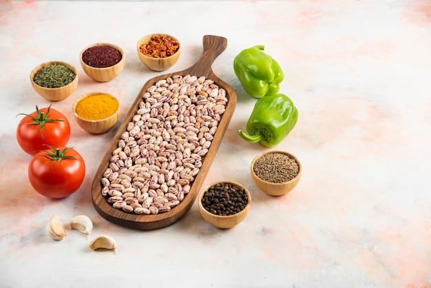 Bovenaanzicht van stapel bonen op een houten bord met verse groenten en kruiden.