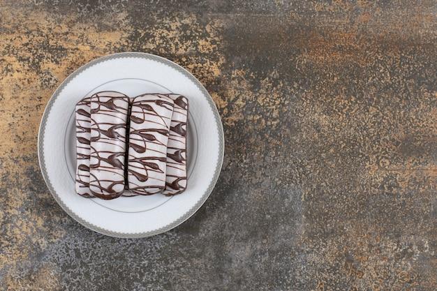 Bovenaanzicht van stapel chocoladekoekjes op witte plaat.