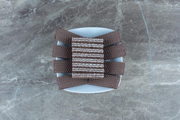 Bovenaanzicht van stapel chocoladewafels in witte kom.
