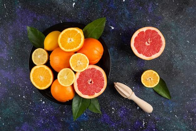 Bovenaanzicht van stapel fruit op zwarte plaat.