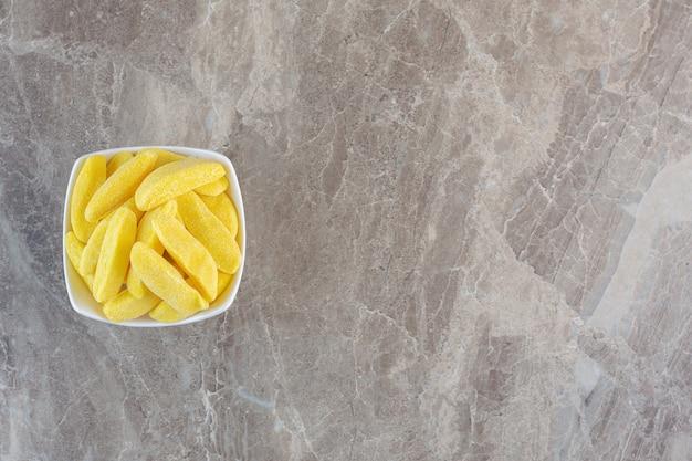 Bovenaanzicht van stapel gele snoep in witte kom.