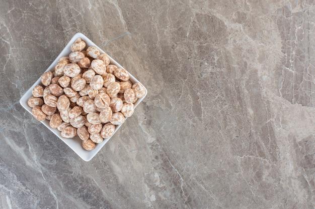 Bovenaanzicht van stapel karamel snoepjes in witte kom over grijze achtergrond.