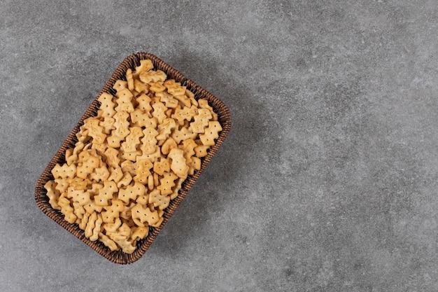 Bovenaanzicht van stapel kleine koekjes in mand over grijze tafel.