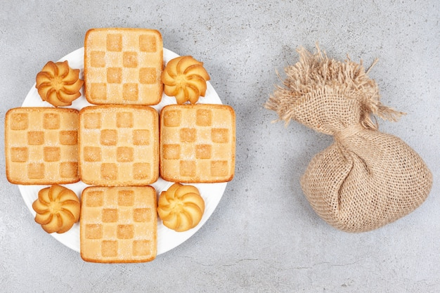 Bovenaanzicht van stapel koekjes op witte plaat en zak op grijze tafel.