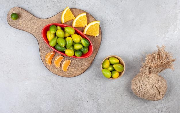 Bovenaanzicht van stapel kumquats in rode kom met sinaasappel- en mandarijnplakken op houten snijplank