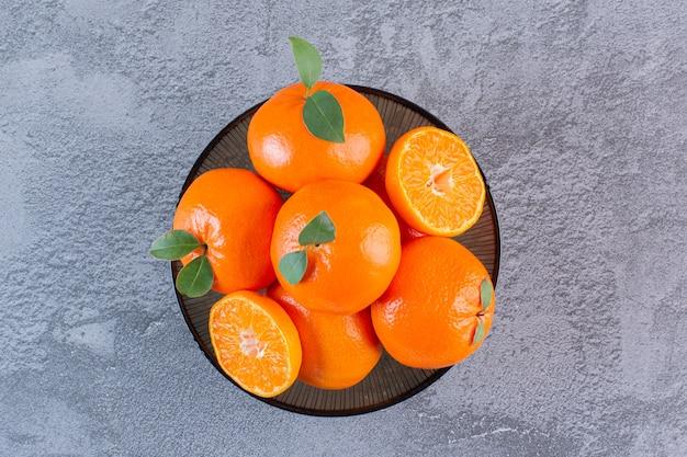 Bovenaanzicht van stapel mandarijnen in kom over grijs.
