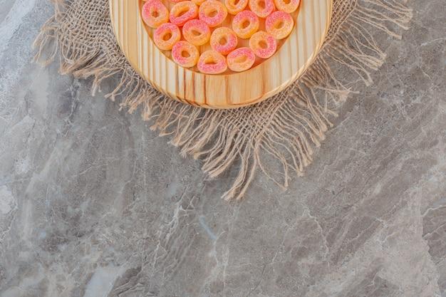 Bovenaanzicht van stapel oranje snoepjes in ringvorm op houten plaat.