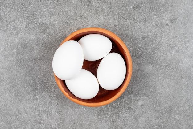 Bovenaanzicht van stapel rauwe eieren in aardewerk kom over grijs oppervlak.