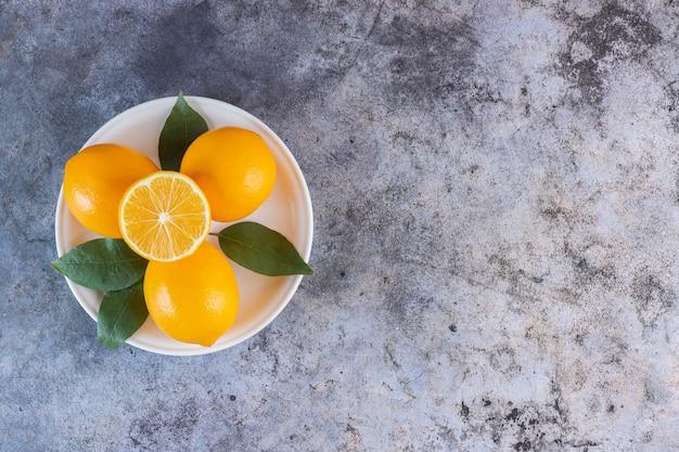 Bovenaanzicht van stapel rijpe citroenen op witte plaat over grijs.