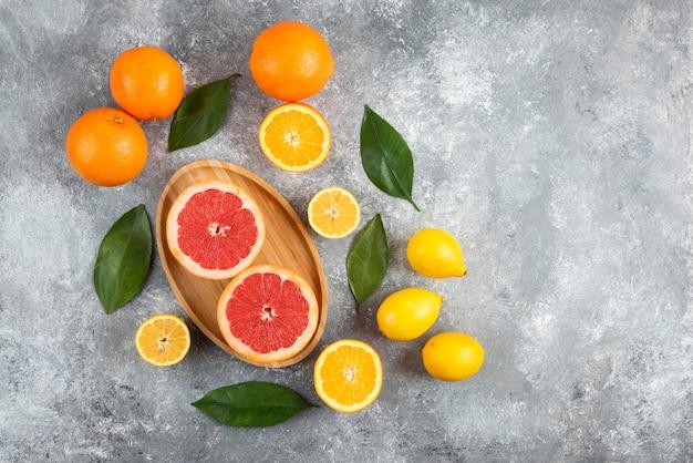 Bovenaanzicht van stapel vers fruit over grijze tafel.