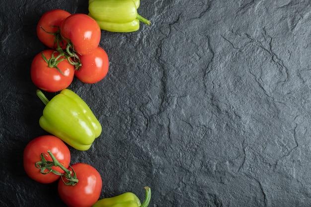 Bovenaanzicht van stapel verse groenten. tomaten en paprika's].