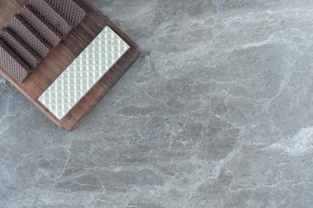 Bovenaanzicht van stapel wafels in houten plank over grijze achtergrond.