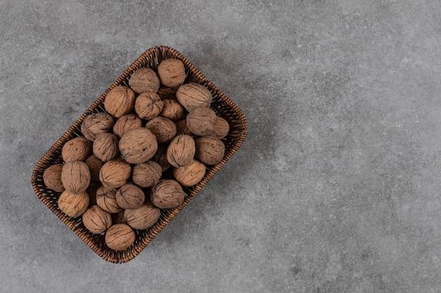 Bovenaanzicht van stapel walnoten in mand over grijze tafel.