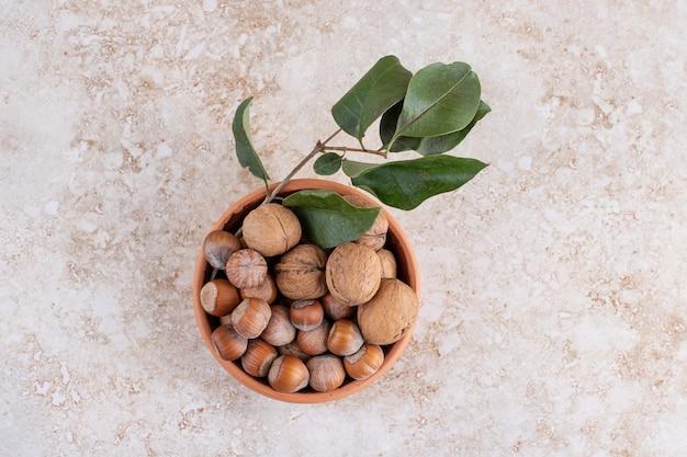 Bovenaanzicht van stapel walnoten met hazelnoten in kom.