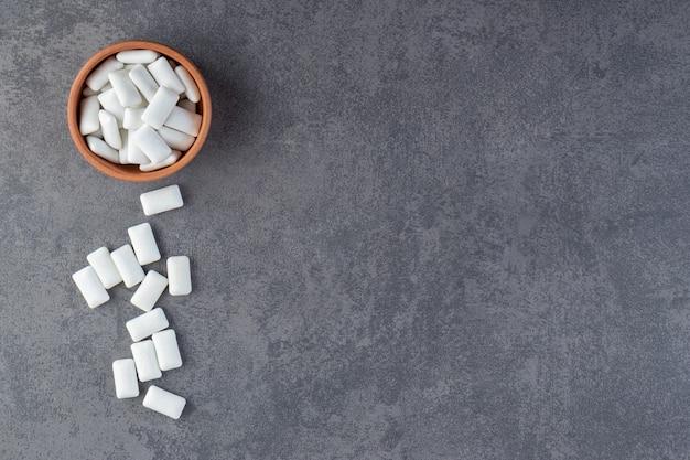 Bovenaanzicht van stapel wit tandvlees in houten kom over grijze achtergrond.