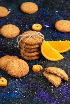 Bovenaanzicht van stapel zelfgemaakte koekjes met sinaasappelschijfje over donkere tafel.