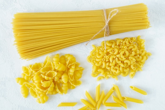 Bovenaanzicht van stapelbedden van verschillende soorten pasta op een lichte ondergrond