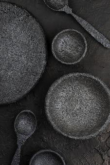 Bovenaanzicht van stenen kommen en lepels op leisteen