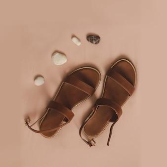 Bovenaanzicht van stijlvolle vrouwelijke sandalen met zee kiezels op beige achtergrond vakantie op zee concept