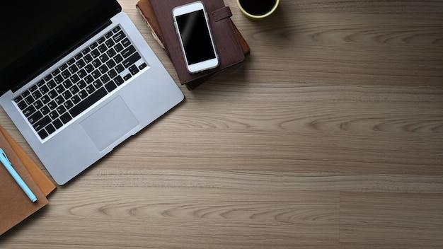 Bovenaanzicht van stijlvolle werkruimte met laptop, smartphone, koffiekopje, notebook en kopieerruimte op houten tafel.