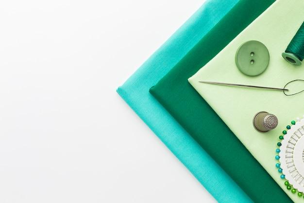 Bovenaanzicht van stoffen met naald en vingerhoed