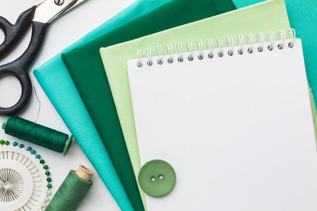 Bovenaanzicht van stoffen met notitieboekje en draad