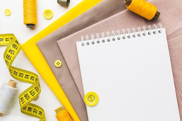 Bovenaanzicht van stoffen met notitieboekje en meetlint