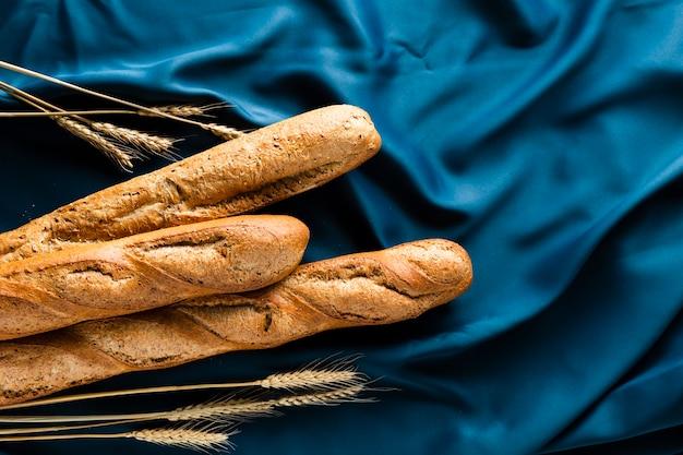 Bovenaanzicht van stokbrood en tarwe op blauw materiaal