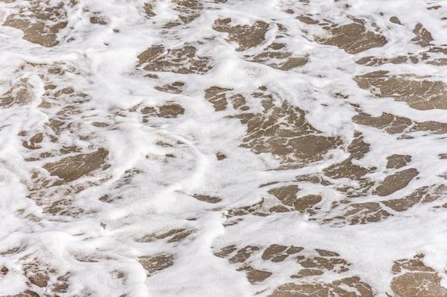 Bovenaanzicht van strand met water en schuim