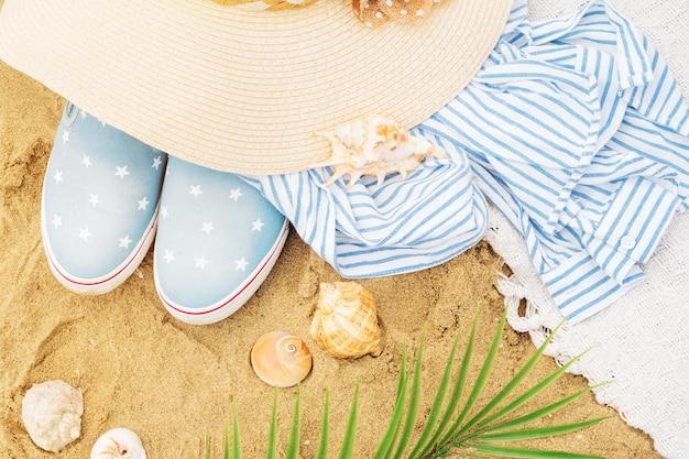 Bovenaanzicht van strandaccessoires op het zand. hoed, gestreept overhemd, schelpen, palmtakken en slip-on sneakers voor een tropische trip. zomervakantie.