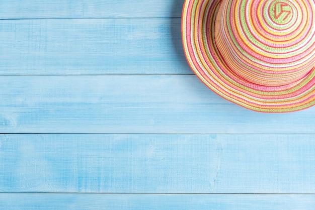 Bovenaanzicht van strooien hoed reistoebehoren op lichtblauwe houten plankenvloer voor zomervacatio