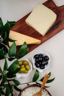 Bovenaanzicht van stukjes kaas op een houten snijplank met ingelegde olijven op witte tafel