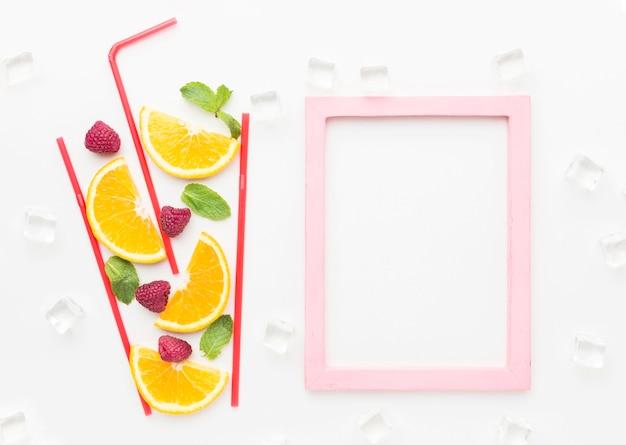 Bovenaanzicht van stukjes sinaasappel in stro glas met munt en frame