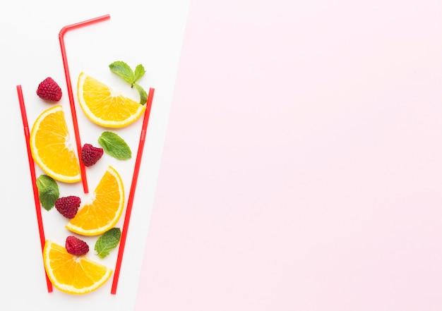 Bovenaanzicht van stukjes sinaasappel in stro glas met munt en kopieer ruimte