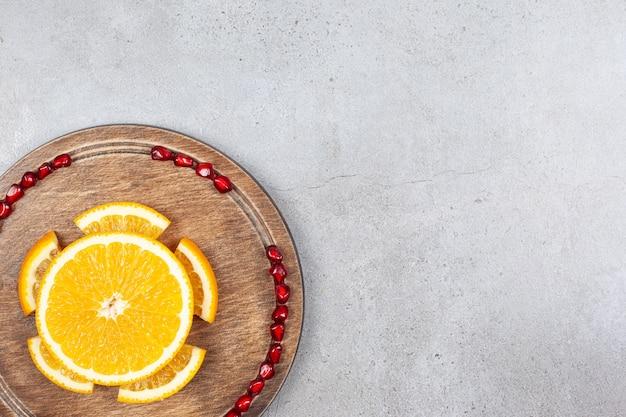 Bovenaanzicht van stukjes sinaasappel met granaatappel zaden op houten bord over grijs oppervlak.